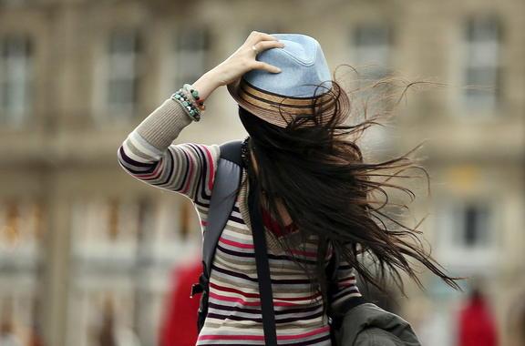Una mujer se sostiene el sombrero mientras lucha contra el viento en Colonia (Alemania). / EFE