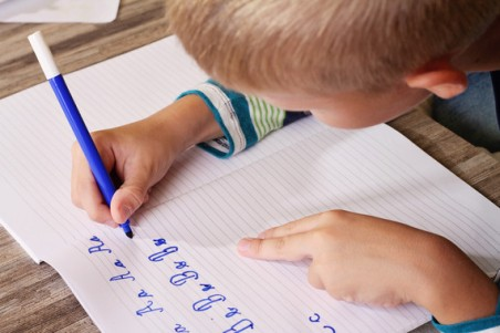 School Boy Writing on Paper writing the alphabet with Pencil . Kid, homework, education concept